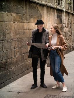 Amigos bonitos e de estilo andando com mapa e câmera pela rua.