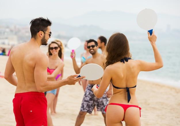 Amigos brincando com raquetes na praia