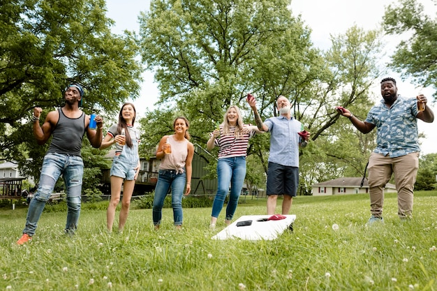 Amigos brincando de cornhole em uma festa de verão no parque