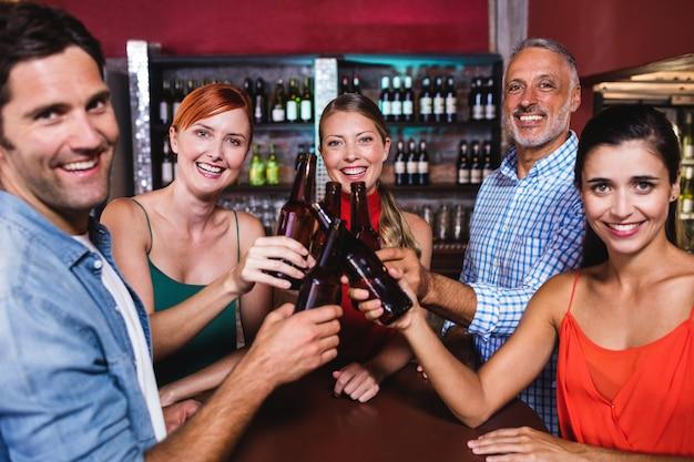 Amigos brindando a garrafa de cerveja na boate