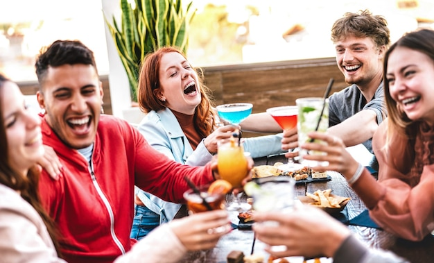 Amigos brindando bebidas multicoloridas em bar restaurante ao ar livre depois do trabalho