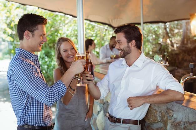 Amigos brindando copo e garrafa de álcool no balcão do restaurante