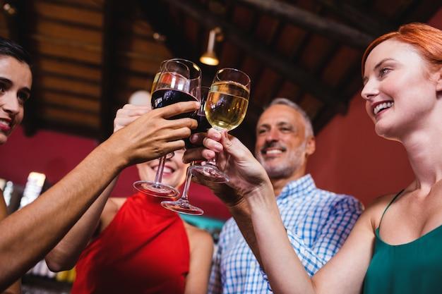 Amigos brindando o copo de vinho na boate