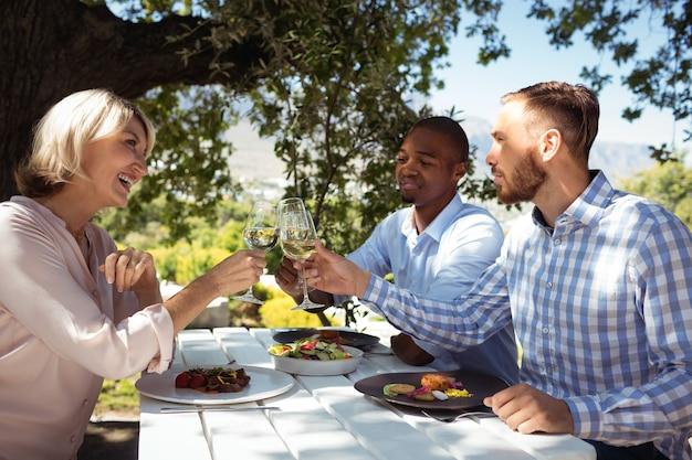 Amigos brindando taças de champanhe em restaurante