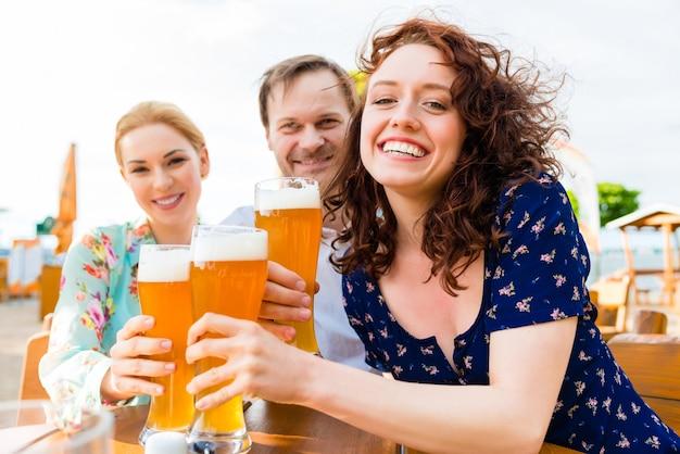 Amigos, brindar, com, cerveja, em, jardim, restaurante