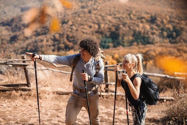 Amigos, caminhadas na montanha. homem apontando no caminho certo. mochilas nas costas.