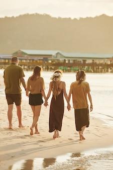 Amigos caminhando na praia do mar