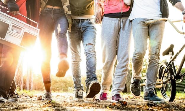 Amigos caminhando no parque da cidade com luz de fundo e auréola solar