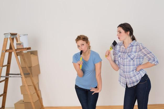 Amigos cantando em pincéis por escada em uma nova casa