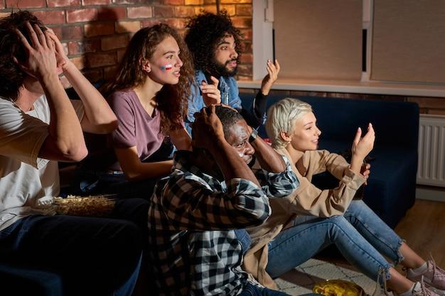 Amigos chateados pelo time de futebol em casa, torcendo pelo time favorito, preocupam-se. sentar no sofá em casa, no quarto escuro à noite