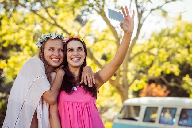 Amigos, clicando em selfie em telefones móveis
