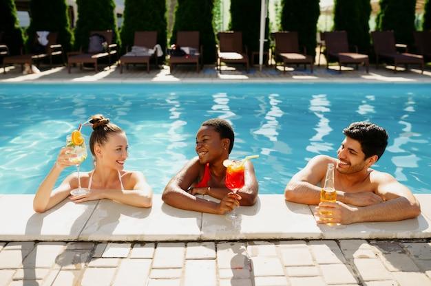 Amigos com bebidas posam na beira da piscina
