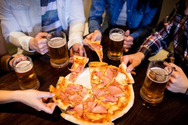 Amigos com caneca de cerveja e pizza no bar