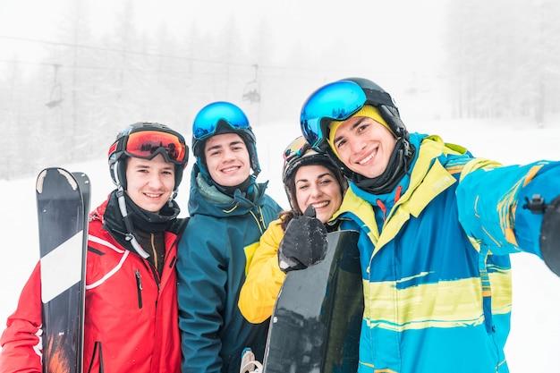 Amigos com esqui e snowboard tirando uma selfie nas encostas