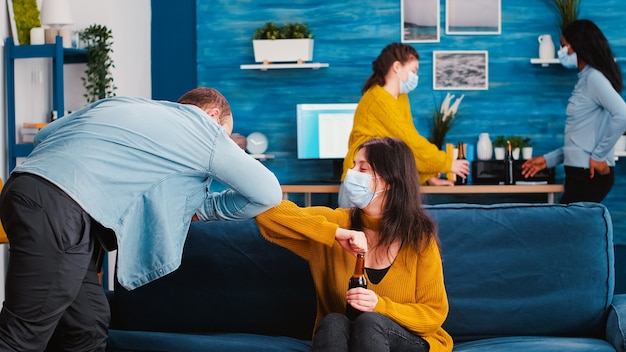 Amigos com máscara médica protetora cumprimentam seus cotovelos mantendo o distanciamento social
