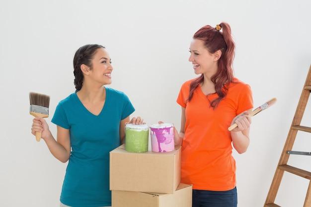 Amigos com pincéis, latas e caixas em uma nova casa