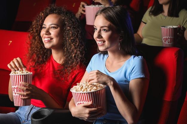 Amigos com pipoca assistindo filme no cinema