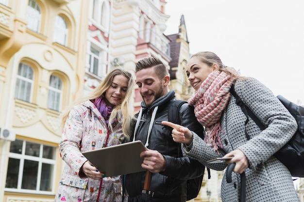 Amigos com tablet na rua antiga