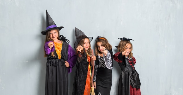 Amigos com trajes de vampiros e bruxas para as férias do dia das bruxas apontando para a frente