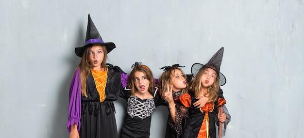 Amigos com trajes de vampiros e bruxas para as festas do dia das bruxas fazendo uma piada