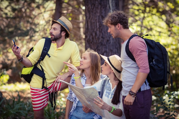 Amigos com um mapa olhando para uma direção