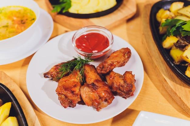 Amigos comemoram com alimentos orgânicos na vista superior de mesa de madeira. homens e mulheres passam pratos um para o outro.