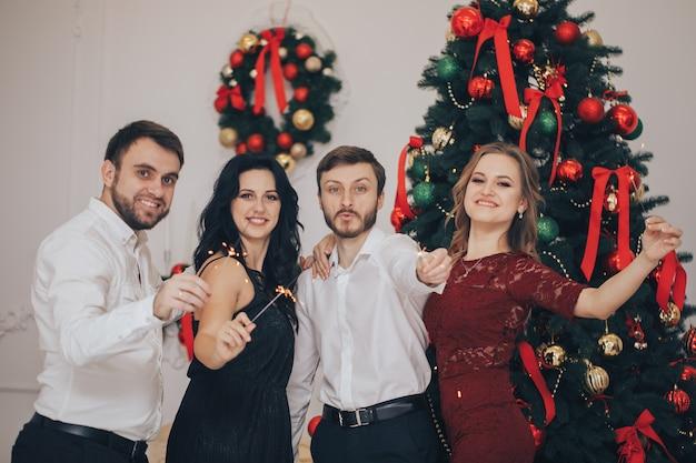 Amigos comemorando a festa de véspera de natal ou ano novo com luzes de bengala