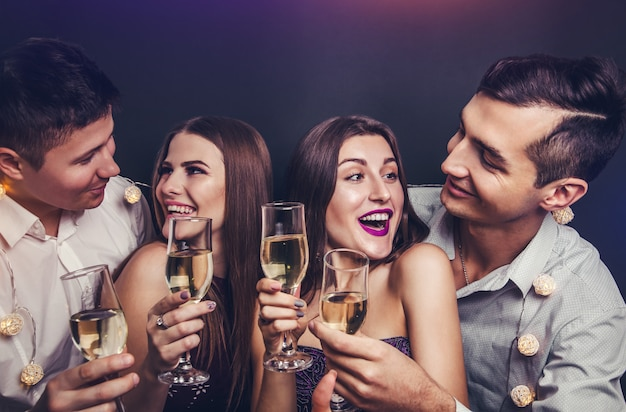 Amigos comemorando a véspera de ano novo, bebendo champanhe e acendendo estrelinhas na festa de máscaras