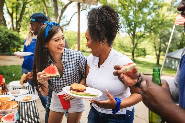 Amigos comemorando e comendo em uma festa ao ar livre