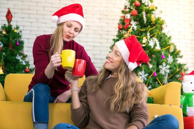 Amigos comemorando o natal ou o ano novo e as mãos segurando um copo colorido Foto Premium