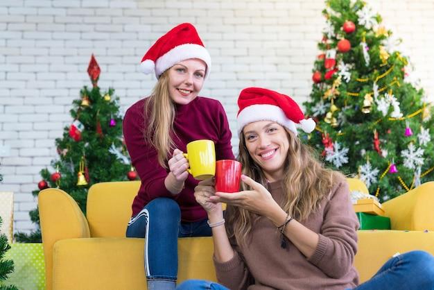 Amigos comemorando o natal ou o ano novo e as mãos segurando um copo colorido