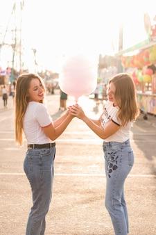 Amigos comendo algodão doce no parque de diversões