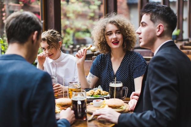 Amigos comendo e conversando no restaurante