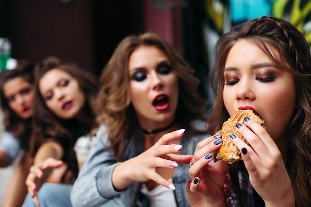 Amigos comendo fast-food contra pichações.