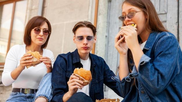Amigos comendo hambúrgueres ao ar livre