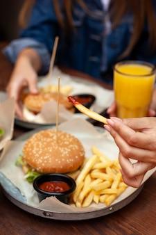 Amigos comendo hambúrgueres com batatas fritas
