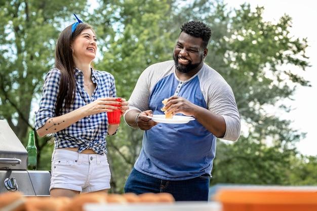 Amigos comendo hambúrgueres em uma festa ao ar livre