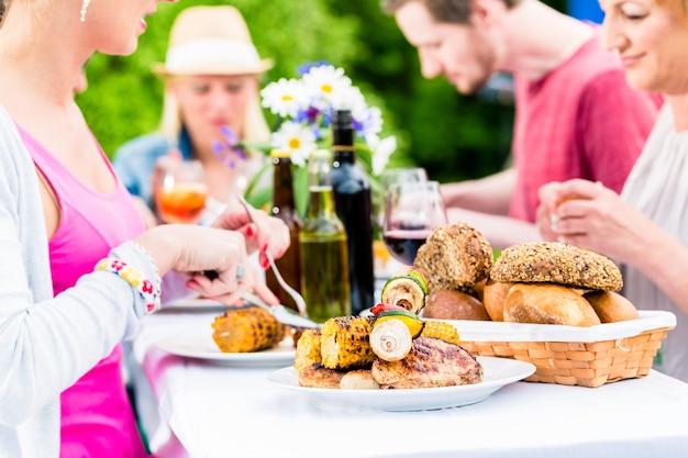 Amigos comendo linguiça e carne para churrasco em uma festa no jardim ou na churrasqueira