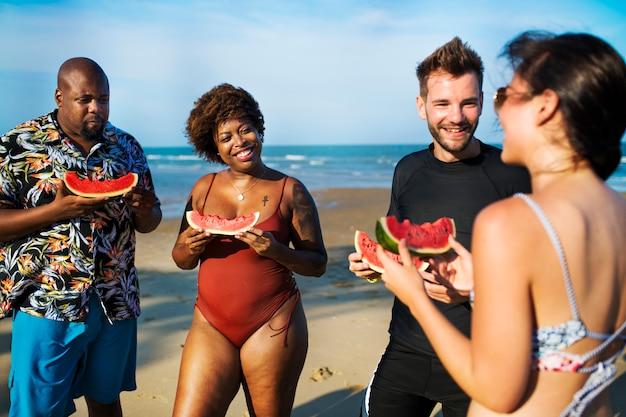 Amigos, comendo melancia, praia