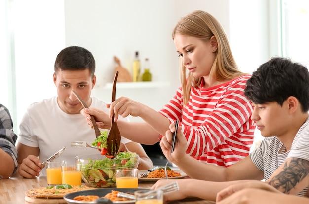 Amigos comendo na mesa da cozinha