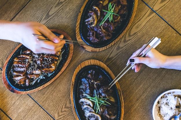 Amigos comendo pato crocante coreano e bulgogi com pauzinhos