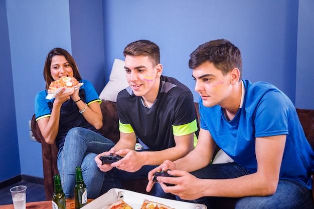 Amigos comendo pizza e assistindo futebol