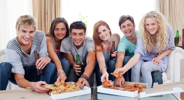 Amigos comendo pizza em casa
