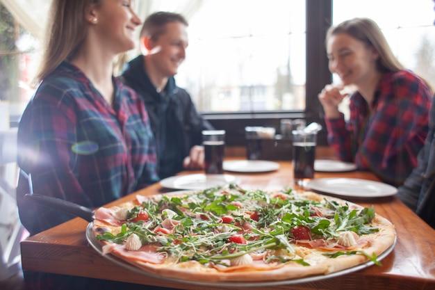 Amigos comendo pizza juntos