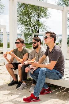 Amigos, comendo pizza, ligado, praia