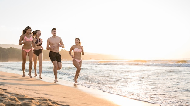 Amigos completos correndo juntos na costa