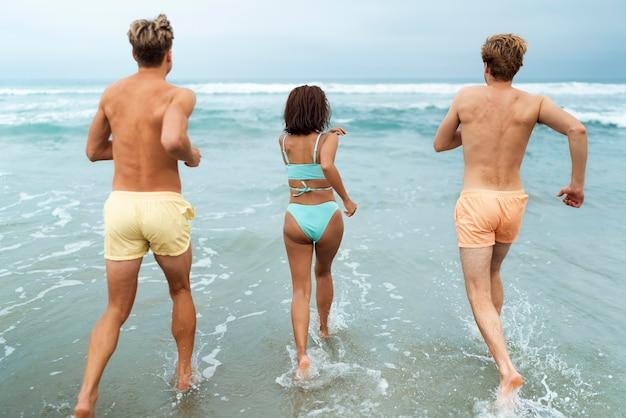 Amigos completos correndo no mar
