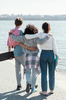 Amigos completos juntos à beira-mar