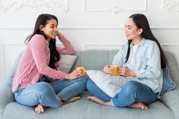 Amigos, conversando, enquanto, sentar sofá