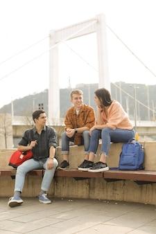 Amigos conversando, sentado em um banco